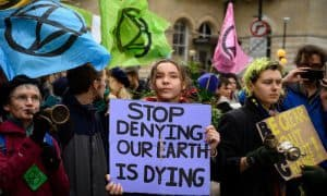Image of protest placard: Stop denying our earth is dying.